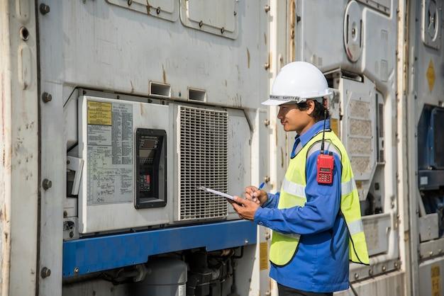 Arbeiter, der die kühlbox des kühlcontainers in der logistikzone überprüft