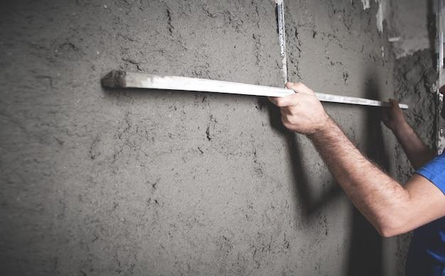 Arbeiter, der ebenes werkzeug hält verputzwand bauarbeiten arbeit heimindustrie
