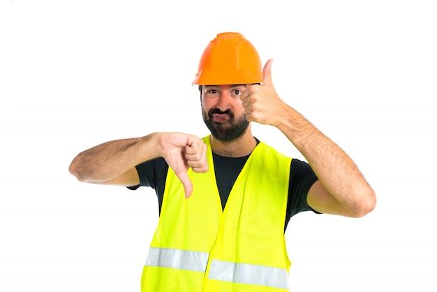 Arbeiter, der ein gut-schlechtes zeichen über weißem hintergrund bildet