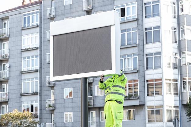 Arbeiter, der ein neues elektronisches schild auf stadtstraße installiert