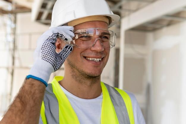 Arbeiter, der eine schutzbrille auf einer baustelle trägt