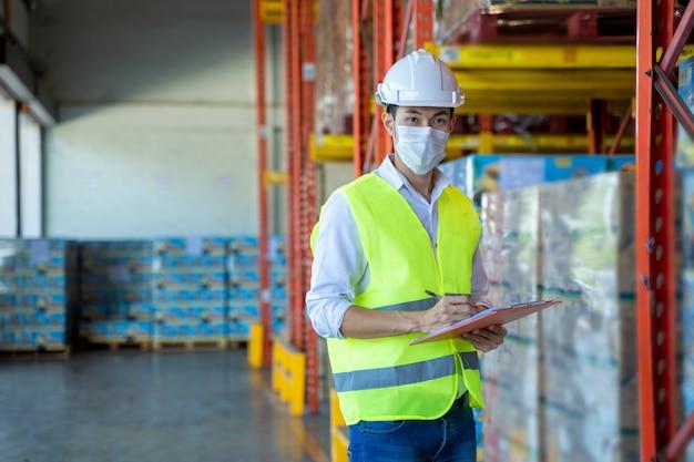 Arbeiter, der eine schutzmaske trägt, um sich vor covid-19 zu schützen und das produkt in einem großen lager zu überprüfen.
