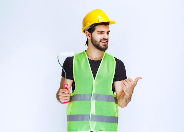 Arbeiter, der eine weiße trimmwalze für die wandmalerei hält.