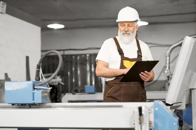 Arbeiter der fabrik, die ordner hält und laserschneider beobachtet.