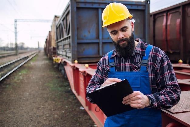 Arbeiter, der frachtcontainer für schifffahrtsunternehmen per güterzug versendet und waren für den export organisiert