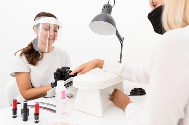 Arbeiter, der gesichtsschutz am nagelstudio trägt