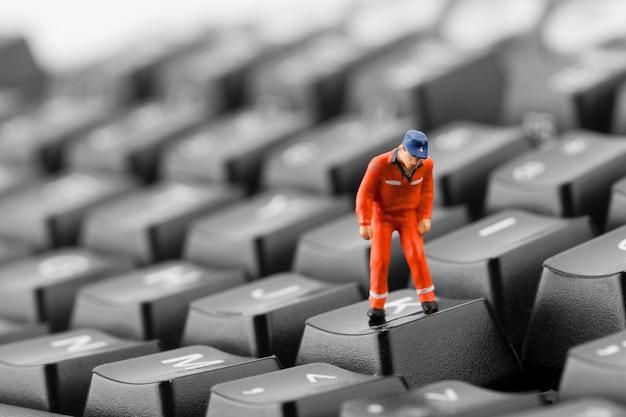 Arbeiter, der in grube in tastatur schaut