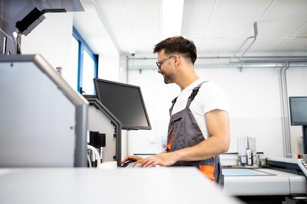 Arbeiter, der industriemaschinen in automatisierter fabrik betreibt.