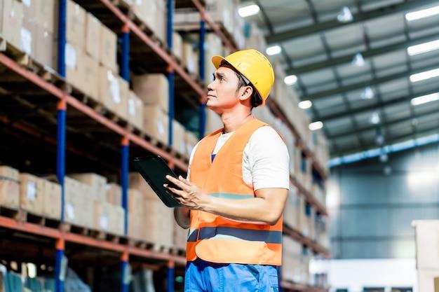 Arbeiter, der inventar im logistiklager nimmt