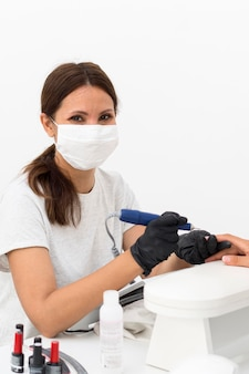 Arbeiter, der maske am nagelstudio trägt