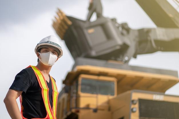 Arbeiter, der maske im braunkohle- oder kohlebergbau mit dem lkw trägt, der kohle transportiert.