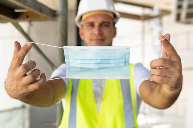 Arbeiter, der medizinische maske auf einer baustelle trägt
