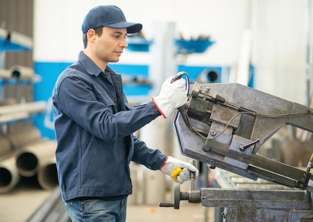 Arbeiter, der mit einem cropper ein eisenrohr in einer fabrik schneidet