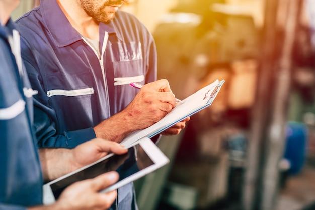 Arbeiter, der mit stift und papier notiz nimmt, mit neuem jungen ingenieur, der computer-tablet verwendet, um schneller und effizienter zu arbeiten.