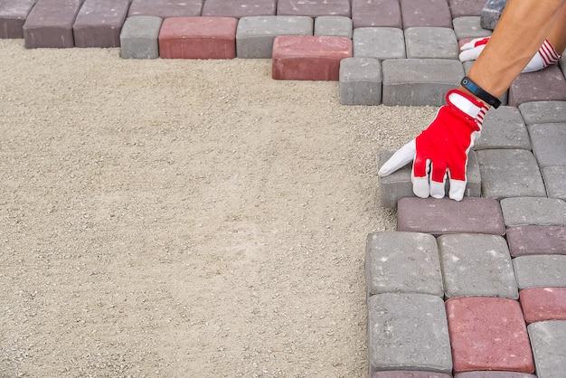 Arbeiter, der pflastersteine legt. steinpflaster, bauarbeiter, der kopfsteinpflasterfelsen auf sand legt.