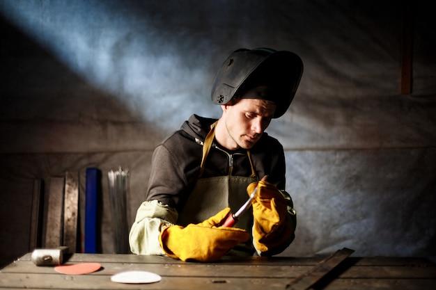 Arbeiter, der plasmaausrüstung in der stahlfabrik hält.