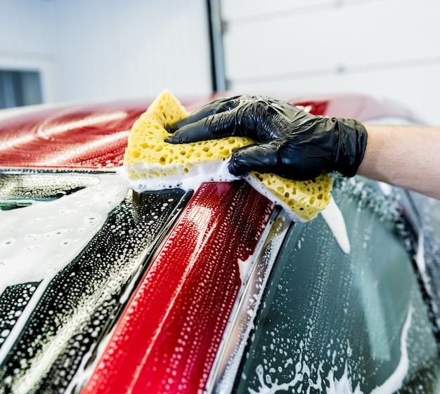 Arbeiter, der rotes auto mit schwamm auf einer autowäsche wäscht.