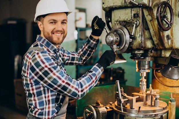 Arbeiter, der schutzhelm trägt, der mit metallkonstruktionen in der fabrik arbeitet