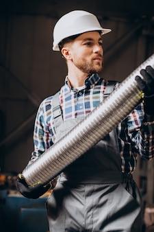 Arbeiter, der schutzhelm trägt, der mit metallrohr in der fabrik arbeitet