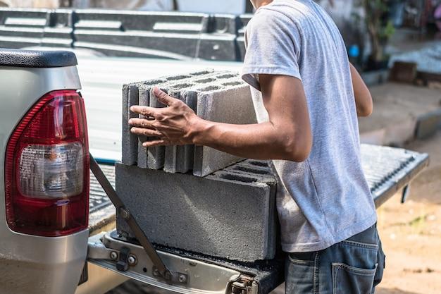 Arbeiter, der schwere baumaterialien von der kofferraumwagenabholung bewegt.