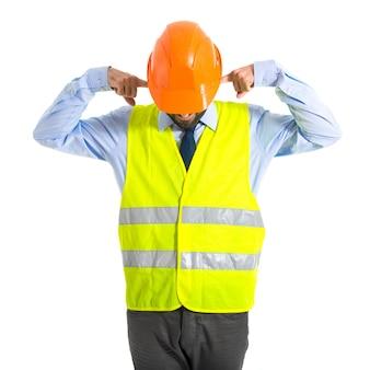 Arbeiter, der seine ohren bedeckt