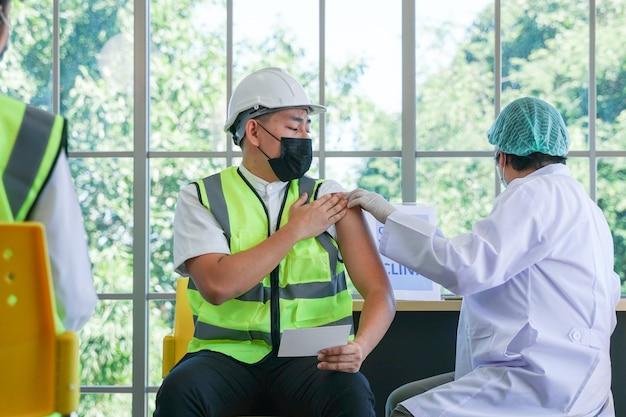 Arbeiter, der sitzt, um einen covid-impfstoff zu bekommen, während eine krankenschwester den impfstoff injiziert, um immunität zu erhalten