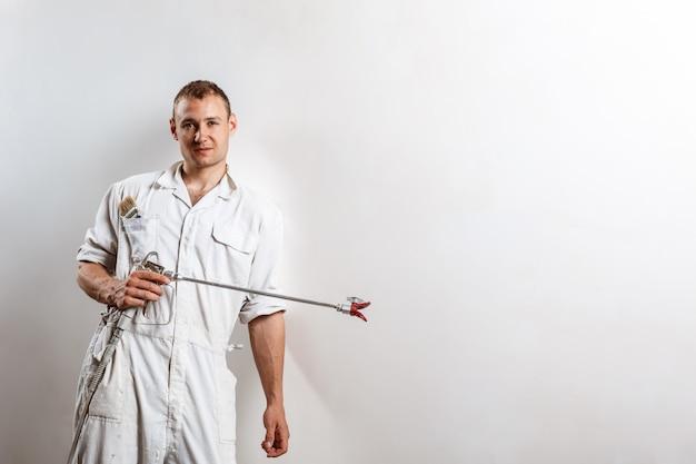 Arbeiter, der spritzpistole auf weißer wand hält.