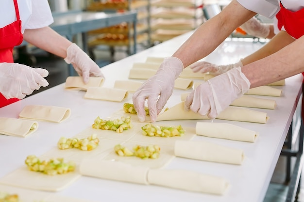 Arbeiter der süßwarenfabrik bereiten desserts mit füllung zu