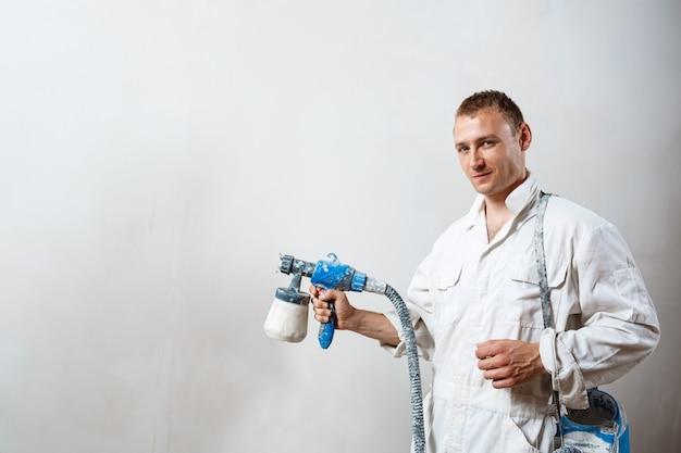 Arbeiter, der wand mit spritzpistole in der weißen farbe malt
