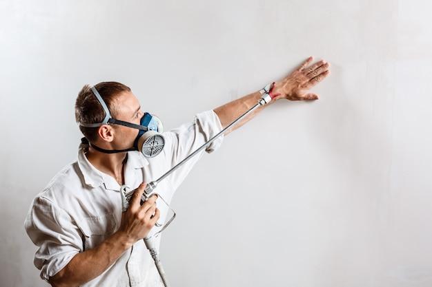 Arbeiter, der wand mit spritzpistole in der weißen farbe malt.