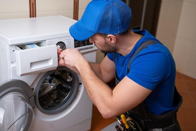 Arbeiter, der waschmaschine im waschraum repariert