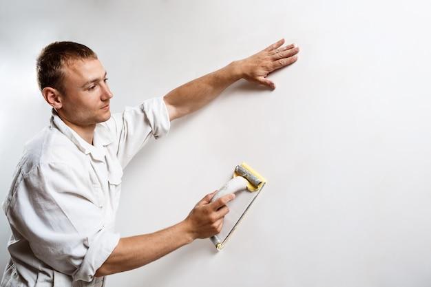 Arbeiter, der weiße wand mit sandpapier schleift.