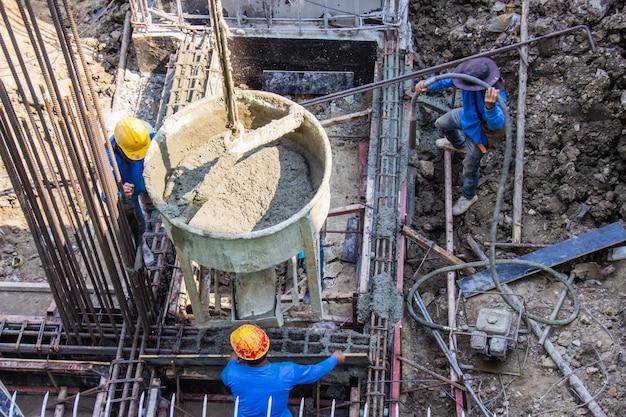 Arbeiter, der zement in fundamentschalung auf der baustelle auf der baustelle gießt.