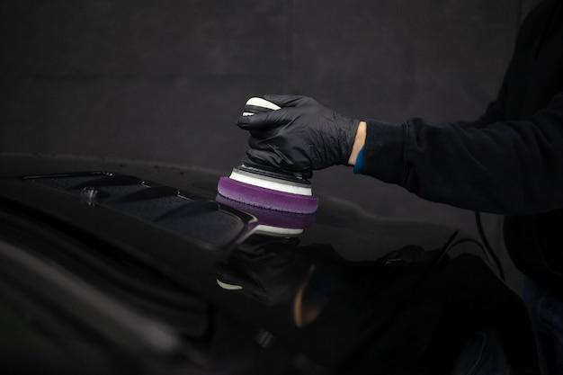 Arbeiter des deteylierungszentrums, der mit einer poliermaschine arbeitet