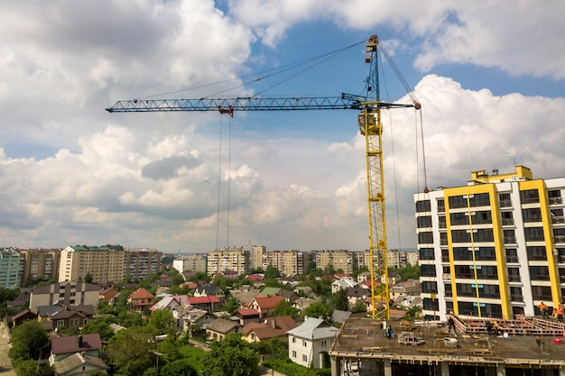 Arbeiter, die an betonrahmen des hohen wohnungsgebäudes im bau in einer stadt arbeiten.