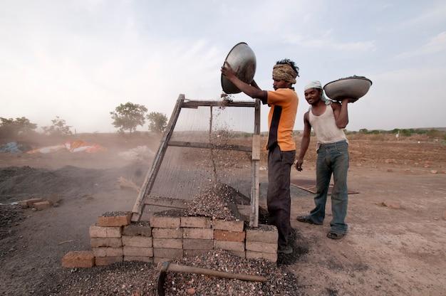 Arbeiter, die auf ton verarbeiten, um traditionelle ziegel in der ziegelfabrik herzustellen