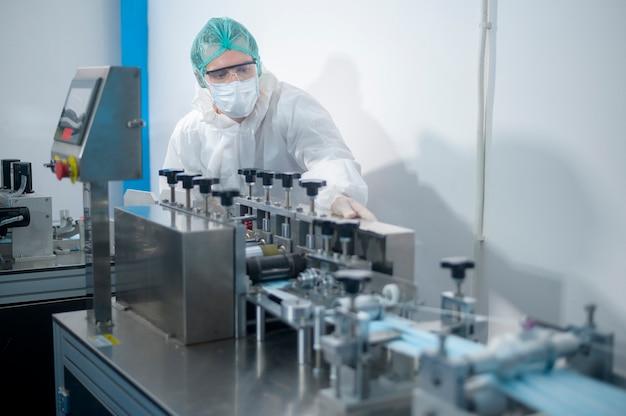Arbeiter, die chirurgische masken in moderner fabrik herstellen, covid-19-schutz und medizinisches konzept.