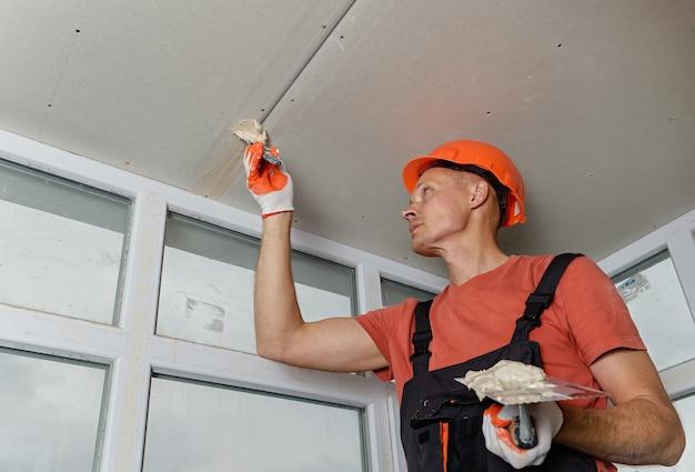 Arbeiter, die die gipskartonplatten füllen, nähen den gipskitt