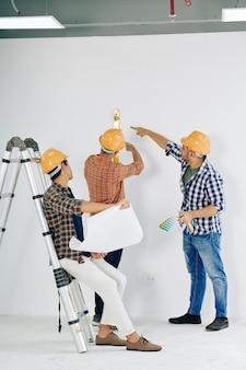 Arbeiter, die die wandhöhe überprüfen