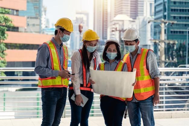 Arbeiter, die eine chirurgische maske und einen weißen sicherheitskopf tragen, um sich vor verschmutzung und viren am arbeitsplatz zu schützen, während sie sich sorgen um eine covid-pandemie machen
