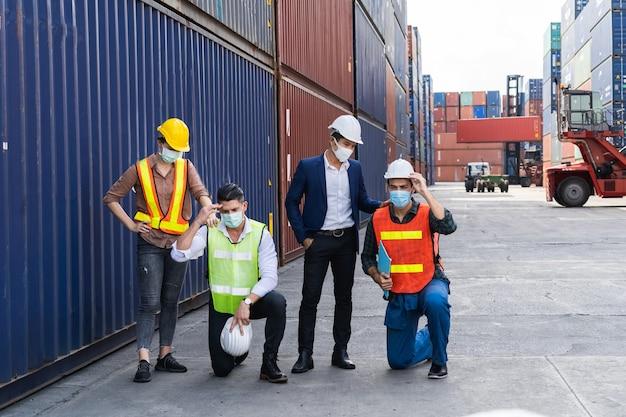 Arbeiter, die eine chirurgische maske und einen weißen sicherheitskopf tragen, um vor verschmutzung und viren am arbeitsplatz zu schützen, während sie sich sorgen über eine kovide pandemie machen