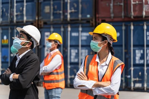 Arbeiter, die eine chirurgische maske und einen weißen sicherheitskopf zum schutz vor verschmutzung und viren am arbeitsplatz tragen