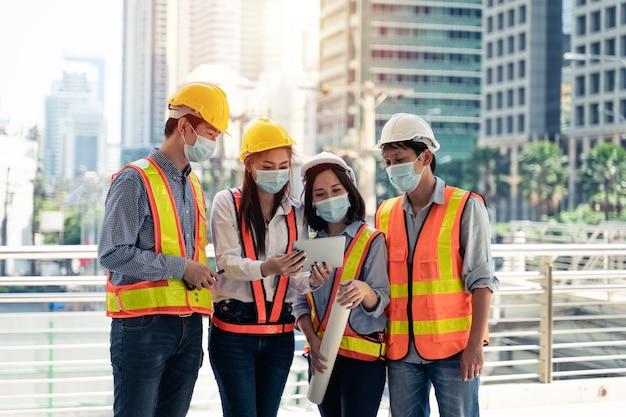Arbeiter, die eine chirurgische maske und einen weißen sicherheitskopf zum schutz vor verschmutzung und viren tragen