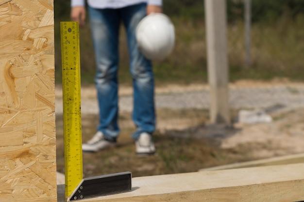 Arbeiter, die einen baumeister verwenden, versuchen quadratisch oder rechtwinklig, um sicherzustellen, dass die isolierte holzwandplatte auf einer baustelle richtig installiert ist installed