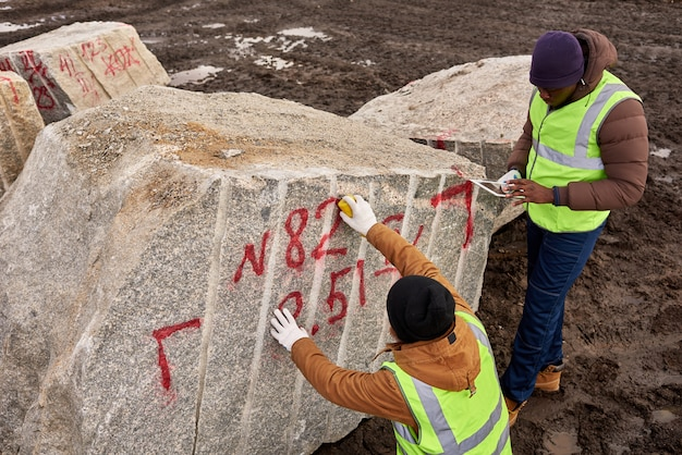 Arbeiter, die granit markieren