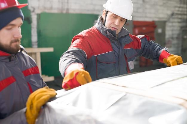Arbeiter, die lasten im lager einwickeln