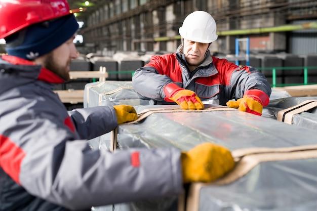 Arbeiter, die lasten in der fabrik bewegen