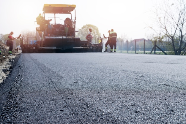 Arbeiter, die neue asphaltbeschichtung auf die straße bringen