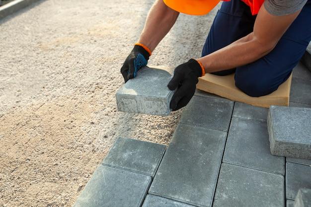 Arbeiter, die pflastersteine weg verkleiden