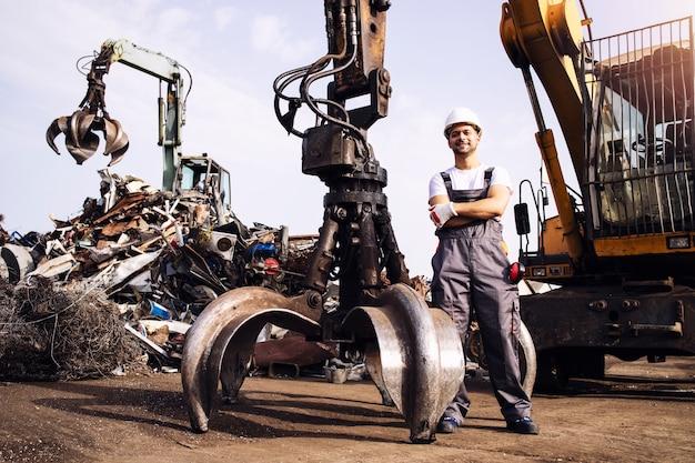 Arbeiter, die von einer hydraulischen industriemaschine zum heben von metallschrottteilen im schrottplatz stehen